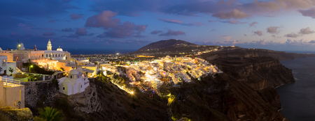 dramatically: Cityscape of Fira, dramatically located on the edge of the caldera cliff on the island of Thira known as Santorini, Greece. Panorama shot at dusk.