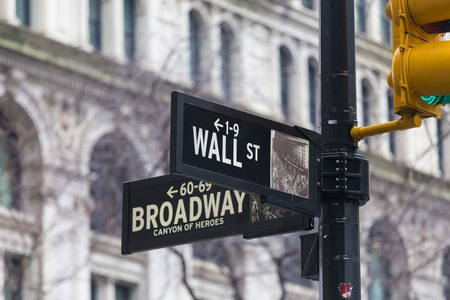 Wall street sign in New York with American flags and New York Stock Exchange background. Foto de archivo