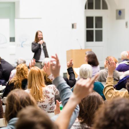 Mam pytanie. Grupa ludzi siedzi na krzesłach w sali konferencyjnej, podnosząc ręce. Warsztaty na uniwersytecie. Biznes i impreza Przedsiębiorczości.
