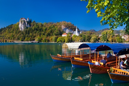 bled: Traditional wooden boats on lake Bled in autumn, with the rocktop castle in the background. Slovenia Stock Photo