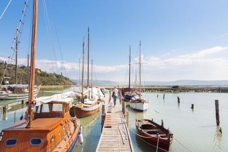 landscape format: Woman strolls along wooden pier between traditional fishing boats at old fishing port in Secovlje, Slovenia. Summertime feeling. Landscape format.