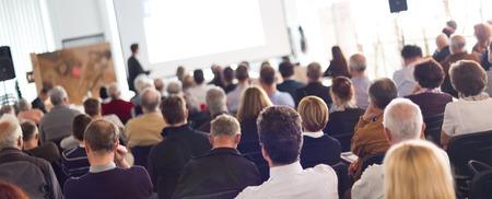 Speaker Het geven van een Talk op zakelijke bijeenkomst. Publiek in de conferentiezaal. Bedrijfsleven en ondernemerschap. Panoramisch samenstelling geschikt voor banners.