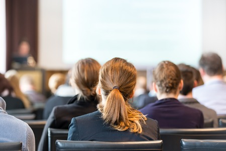 Speaker Giving a Talk at Business Meeting. Audience in the conference hall. Business and Entrepreneurship. Panoramic composition suitable for banners. Stock Photo