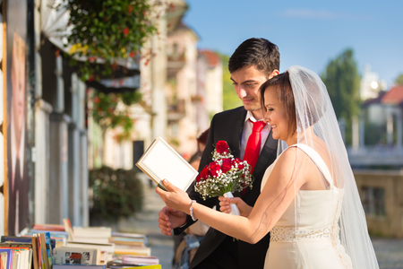 book shop: Bride and groom. Portrait of a loving wedding couple reviewing vintage books in antique book shop in medieval city center of Ljubljana, Slovenia. Stock Photo