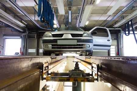 car shop: Car waiting for inspection an service platform in car repair shop. Stock Photo