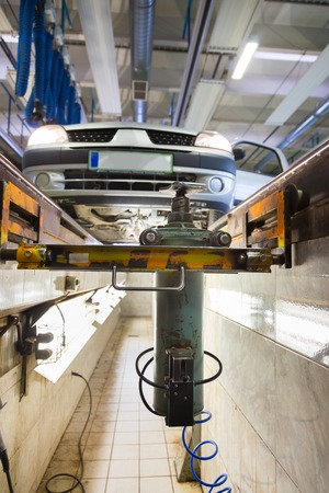 reparations: Car waiting for inspection an service platform in car repair shop. Stock Photo