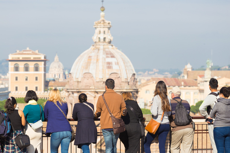 Rear view group of tourists on sightseeing tour looking at view of cathedral in Rome, Italy.
