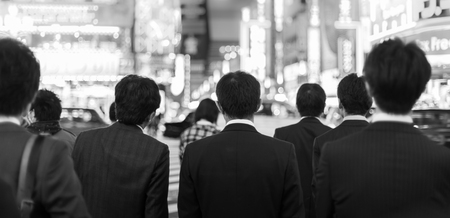 black boards: Japanese corporative business people in suits, waiting in rush hour on crossroad in Shinjuku business district, Tokyo, Japan. Blured advertising boards illuminated in the background. Black and white.