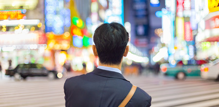 corporative: Solitary japanese corporative businessman in suit, after work, waiting on crossroad in Kabukicho, entertainment and red-light district in Shinjuku, Tokyo, Japan. Stock Photo
