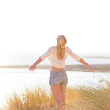 girl in nature: Relaxed woman enjoying freedom and life an a beautiful sandy beach.  Young lady feeling free, relaxed and happy. Concept of happiness, enjoyment and well being.  Enjoying Sun on Vacations. Copyspace. Stock Photo