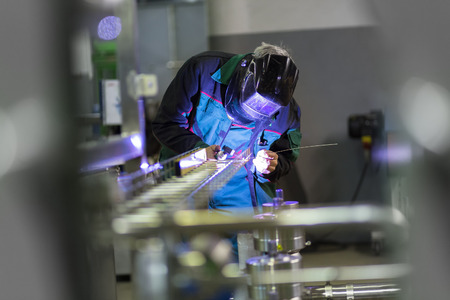 manual: Industrial worker with protective mask welding inox elements in steel structures manufacture workshop or metal factory. Stock Photo