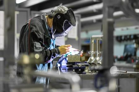 asamblea: Trabajador industrial con la máscara protectora inox elementos de soldadura en la fabricación de estructuras de acero taller o fábrica de metal.