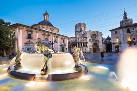 historic site: Square of Saint Marys, fountain Rio Turia and cathedral in background at dusk in Valencia, Spain.