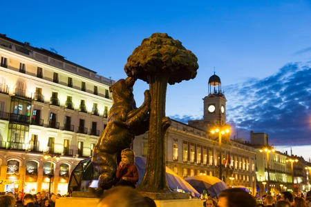 streetlife: Statue of bear and madrone tree, famous symbol of city of Madrid on busy Puerta del Sol square at dusk, Spain. Stock Photo