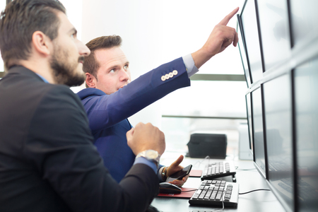 stock traders: Businessmen trading stocks. Stock traders looking at graphs, indexes and numbers on multiple computer screens. Colleagues in discussion in traders office. Business success concept.
