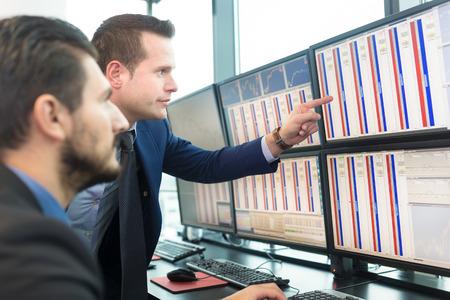 ejecutivo en oficina: Los hombres de negocios el comercio de acciones. Comerciantes Imagenes mirando gr�ficos, �ndices y n�meros en m�ltiples pantallas de ordenador. Colegas en la discusi�n de los comerciantes de la oficina. Concepto de �xito del negocio. Foto de archivo