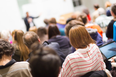 Spreker geeft presentatie in collegezaal op de universiteit. Deelnemers luisteren naar lezingen en het maken van notities.