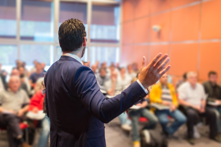 Ponente en la Conferencia de negocios con presentaciones públicas. Audiencia en la sala de conferencias. Club de Emprendimiento. Vista trasera. Composición Horisontal. Desenfoque de fondo.