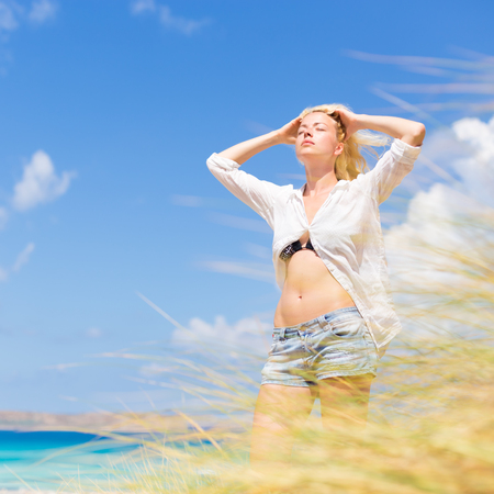 sun: Relaxed woman enjoying freedom and life an a beautiful sandy beach.  Young lady feeling free, relaxed and happy. Concept of freedom, happiness, enjoyment and well being.  Enjoying Sun on Vacations.