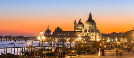 venice: Romantic Italian city of Venice in sunset.   Traditional Venetian wooden boats, gondolier and Roman Catholic church Basilica di Santa Maria della Salute. Stock Photo