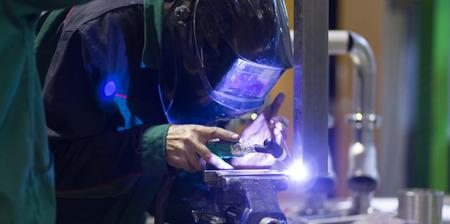 herramientas de trabajo: Trabajador industrial con la máscara protectora elementos inox soldadura de estructuras de acero Fabricación taller.