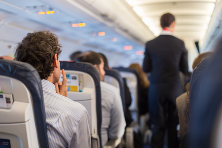 passenger aircraft: Interior of airplane with passengers on seats and steward walking the aisle.