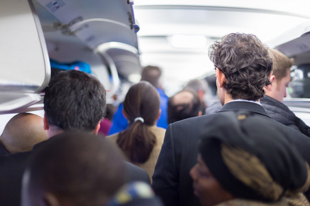 disembark: Interior of airplane with passengers queuing on the aisle, collecting their luggage to disembark plane.