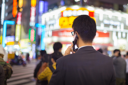 corporative: Japanese corporative businessman in suit, after work, talking on cell phone while waiting on crossroad in Kabukicho, entertainment and red-light district in Shinjuku, Tokyo, Japan. Stock Photo