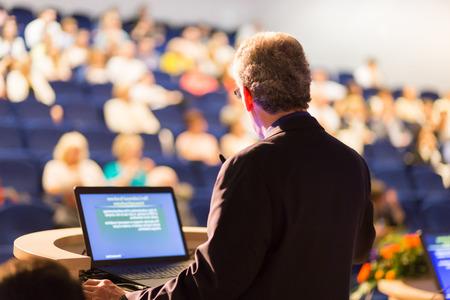 Relatore in conferenza con presentazioni pubbliche. Pubblico presso la sala conferenze. Imprenditorialità club. Vista posteriore. Composizione Horisontal. Sfocatura dello sfondo.