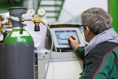 gas cylinder: Industrial operator setting  computer controlled process of orbital welding machine in inox pipes manufacturing workshop. Stock Photo
