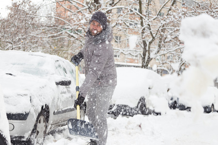 shoveling: Man shoveling her parking lot after a winter snowstorm. Stock Photo