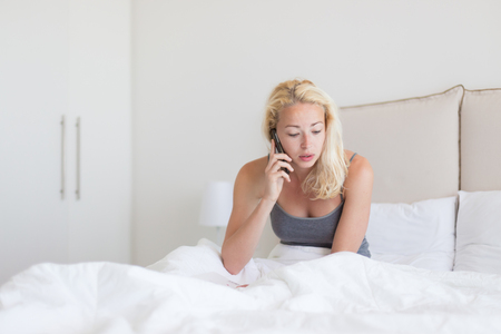 awoken: Portrait of  young lady with mobile phone in bed at home. Tired sleepy woman receiving emergency call in bed early in the morning. Stock Photo