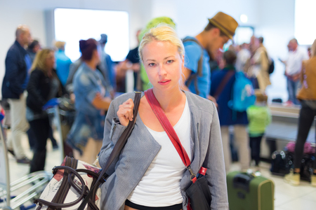 Casually dressed young stylish female traveller waiting in airport arrival terminal hall,  collecting her laggage . Blured background. Can also be used as railway, metro, bus station. Stock Photo