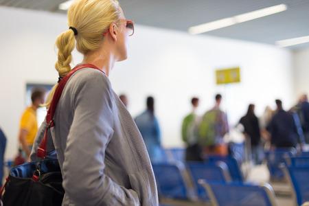 Joven mujer rubia caucsian esperando en la cola. Señora que se coloca en la cola para subir a un avión.