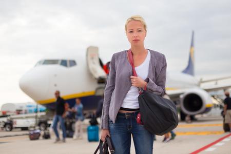 Vestido de manera informal avión desembarco mujer que viajaba con estilo joven. Mujer en los viajes de negocios. Foto de archivo