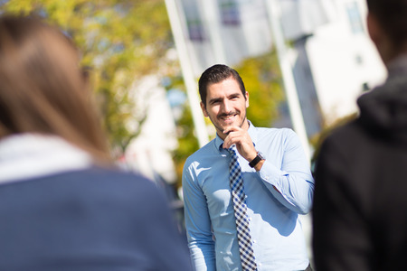 intelligent partnership: Attractive young businessman with a friendly smile having informal out of office meeting on a suny day.