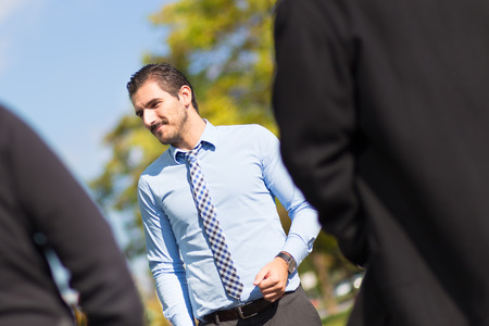 suny: Attractive young businessman with a friendly smile having informal out of office meeting on a suny day.