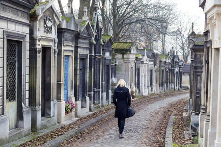 relatives: Solitary woman remembering dead relatives in on Pere Lachaise cemetery in Paris, France. Stock Photo