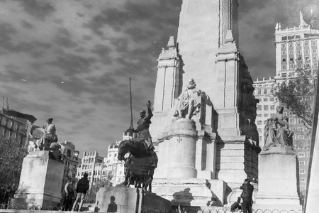 square image: Reflection in water of stone statue of Miguel de Cervantes and bronze sculptures of Don Quixote and Sancho Panza on the Square of Spain, Plaza de Espana, in Madrid. Black and white image.
