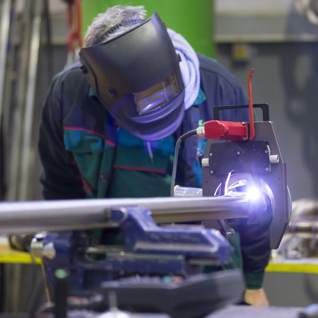 skilled operator: Industrial operator setting  computer controlled process of orbital welding machine in inox pipes manufacturing workshop. Stock Photo