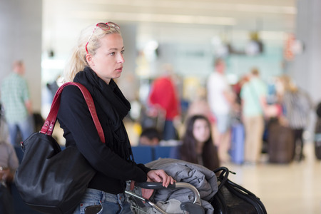 conection: Casual blond young woman using her cell phone while queuing for flight check-in and baggage drop. Wireless network hotspot enabling people to access internet conection. Public transport.