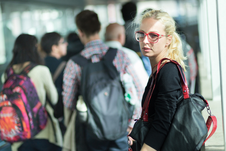 waiting girl: Young blond caucsian woman waiting in queue to board a plane. Stock Photo