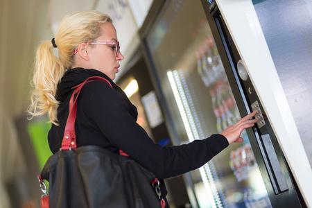 Beiläufige kaukasische Frau, die einen modernen Getränkeautomaten verwendet wird. Ihre Hand ist auf der Wähltastatur platziert, und sie sucht auf dem kleinen Bildschirm. Lizenzfreie Bilder