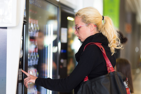 automatic machine: Casual caucasian woman using a modern beverage vending machine. Her hand is placed on the dial pad and she is looking on the small display screen.