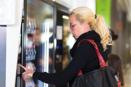 lata de refresco: mujer caucásica ocasional que usa una máquina expendedora de bebidas moderna. Su mano se coloca sobre el teclado de marcación y ella está mirando en la pantalla pequeña.