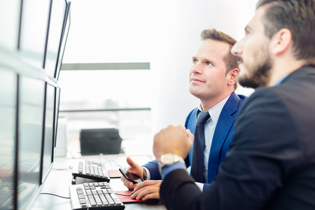 money market: Successful businessmen trading stocks. Stock traders looking at graphs, indexes and numbers on multiple computer screens. Colleagues in traders office. Business success. Stock Photo