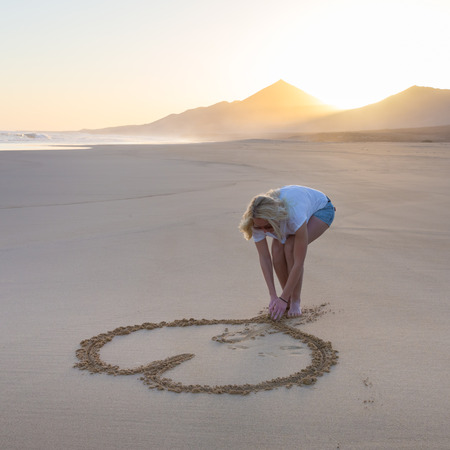 heart in sand: Woman drawing heart in sand on beautiful solitary Cofete beach in sunset. Love, travel concept. Fuerteventura, Canary Islands, Spain.