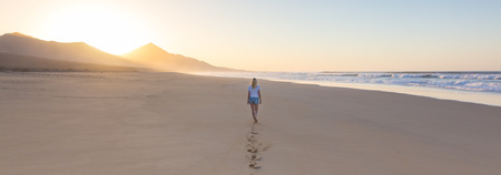Woman walking on sandy beach in sunset leaving footprints in the sand. Beach, travel, concept. Copy space. Panoramic composition. Stock Photo