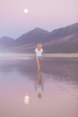 calm woman: Woman walking on sandy beach in dusk leaving footprints in the sand. Beach, travel, concept. Copy space. Vertical composition.