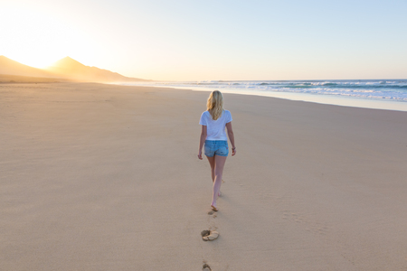 sandy feet: Woman walking on sandy beach in sunset leaving footprints in the sand. Beach, travel, concept. Copy space. Stock Photo